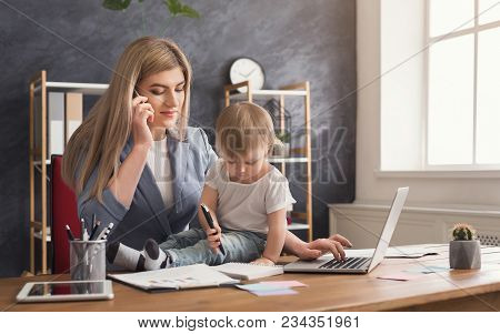 Happy Mother Working At Office With Her Baby. Young Woman Talking On Phone And Using Laptop While Sp