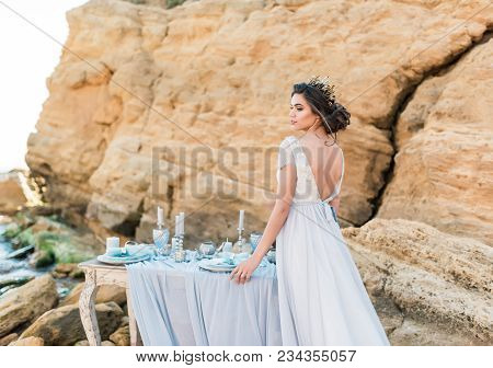 Beautiful Brunette Bride In Light Chiffon Wedding Dress Embroidered With Beads Posing Near The Sea.