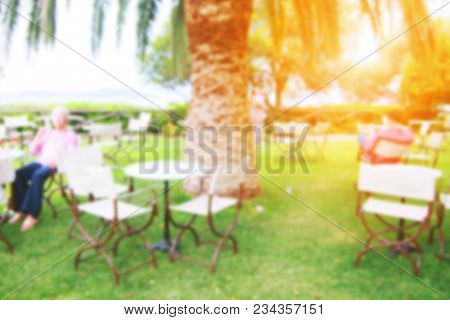 Cafe On A Sea Shore With Green Grass Lawn, Palm Trees, Tables And Chairs For Visitors. Blurred.