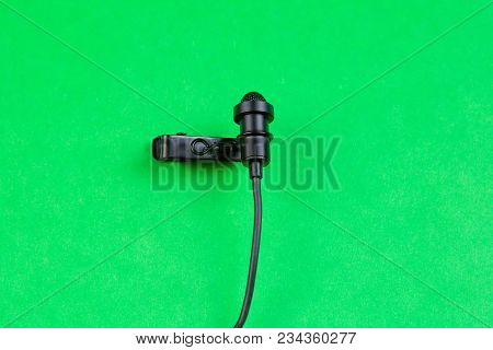 A Small Microphone For Recording Quality Sound On A Green Background.