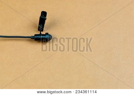 A Small Microphone For Recording Quality Sound On A Brown Background.