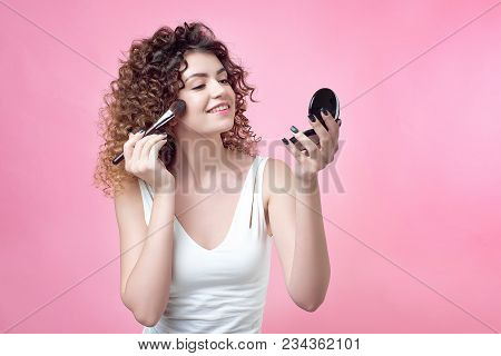 Close-up Of A Young Caucasian Woman Holding Brush And Blush Palette Applying Makeup Isolated On Back
