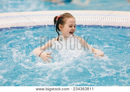 Little child enjoying her time in a hot tub. Bubbly bath. Aquapark.