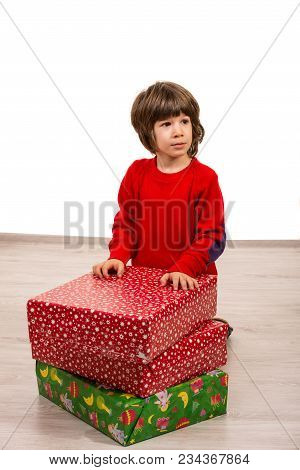 Thinking Boy Sitting On Floor With Christmas Presents And Looking Away