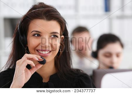 Three Call Centre Service Operators At Work. Portrait Of Smiling Pretty Brunette Woman At Workplace