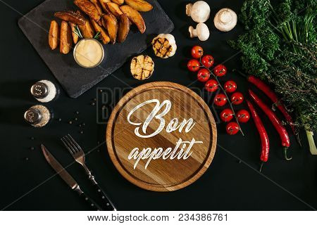 Wooden Board With Inscription Bon Appetit, Baked Potatoes And Vegetables On Black