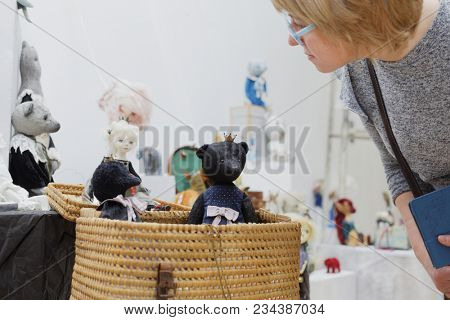 SAINT-PETERSBURG, RUSSIA - MARCH 22, 2018: Visitor looks at the artistic dolls exposed on the exhibition TeddyFun 2018. The exhibition of designed Teddy Bears is held annually since 2011