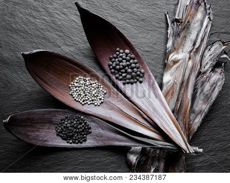 Black, White And Fragrant Piles Of Peppers In Dry Leaf Funnels On Black Stone Background Surface Wit