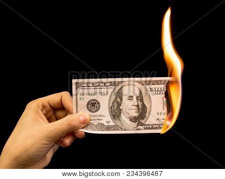 One Hundred Dollars Burn In The Hand On A Black Background .