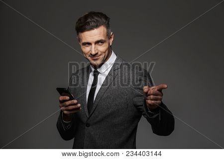 Image of pleased man employer dressed in business costume holding mobile phone and pointing finger on copyspace isolated over gray background