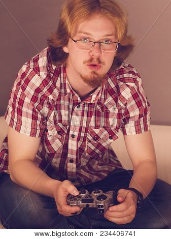 Nerd geek young adult man playing on the video console holding game pad. Gaming gamers concept. poster