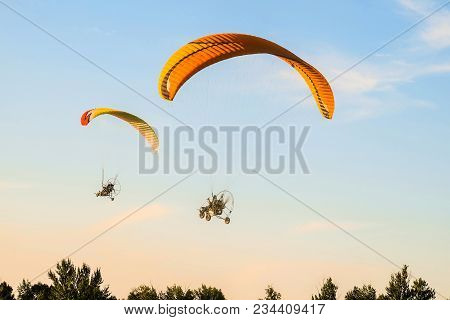 Flight Of Two Motor Paragliders Trike Skyward. Flight On Motor Gliders In The Blue Sky Over The Gree