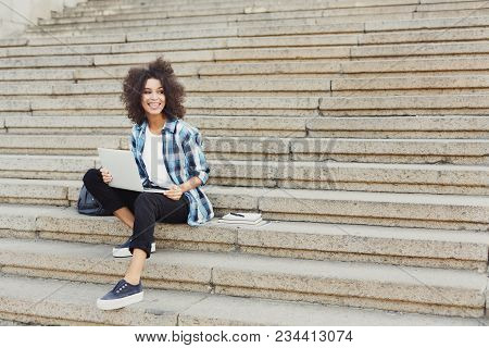 Smiling African-american Student Girl Sitting On Stairs Working With Laptop, Preparing For Exams Out