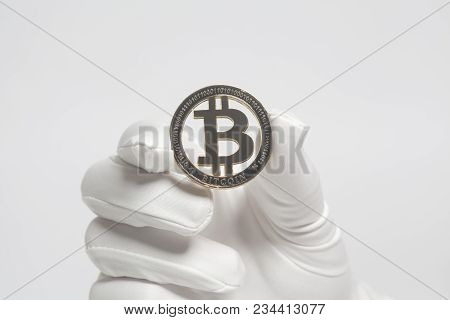 Hand In White Glove Holds Golden Bitcoin Crypto Currency On White.mining Concept.
