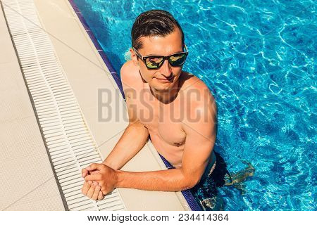Young Handsome Man Having A Good Time In Swimming Pool. All Inclusive. Summer Vacation Concept.