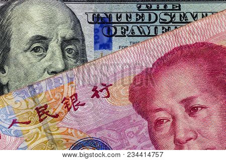 Close Up Of 100 Yuan Banknote  Over A One Hundred Dollar Banknote With Focus On Portraits Of Benjami