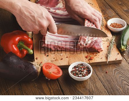 Man Cutting Rack Of Lamb On Wooden Board At Restaurant Kitchen. Chef Preparing Fresh Meat For Cookin