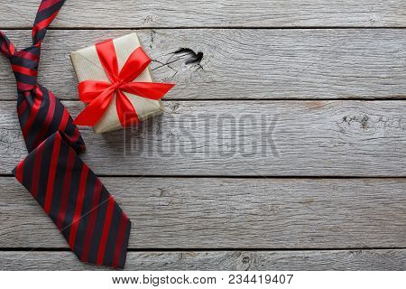 Happy Fathers Day Card With Copy Space, Present And Red And Black Striped Necktie On Rustic Wood Bac