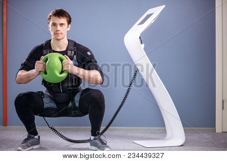 Fit Man In Electric Muscular Suit To Stimulate With Training Medecine Ball