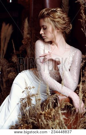 Blonde Bride In Fashion White Wedding Dress With Makeup. Wedding Day Of Bride In Bridal Gown. Beauty