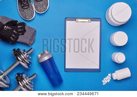 Sports  nutrition (supplements), sneakers, dumbbells and sports accessories on a blue background. Top view with copyspace. Fitness, bodybuilding, sport and healthy lifestyle concept.