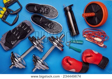 Sport accessories. Boxing gloves, dumbbells, skipping rope, sneakers, wheel exercise,  expander on a blue background.  Top view. Fitness, sport and healthy lifestyle concept.