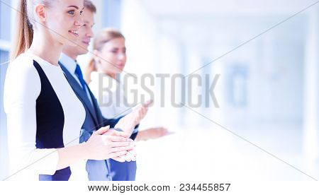 Smiling business people applauding a good presentation in the office . Smiling business people