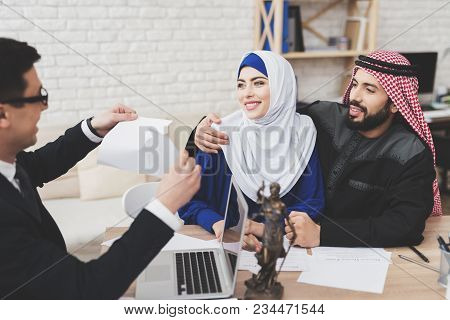 Lawyer In Suit In Office With Arab Husband And Wife. Lawyer Is Tearing Divorce Papers. Couple Is Hap
