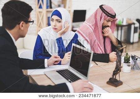 Lawyer In Suit In Office With Arab Husband And Wife. Lawyer Is Talking To Woman.