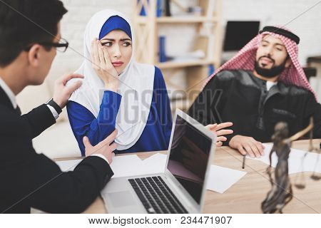 Lawyer In Suit In Office With Arab Husband And Wife. Lawyer Is Comforting Woman.