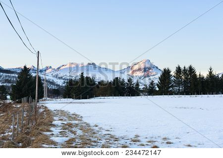 Snowy Field Surrounded By A Fence With Mountains In The Background Bathing In The Setting Sun, Troms