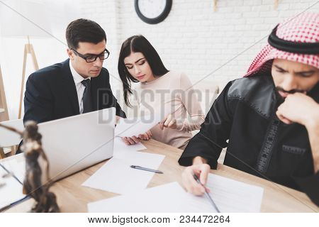 Lawyer In Suit In Office With Arab Husband And Wife. Lawyer Is Helping Woman To Fill Divorce Papers.