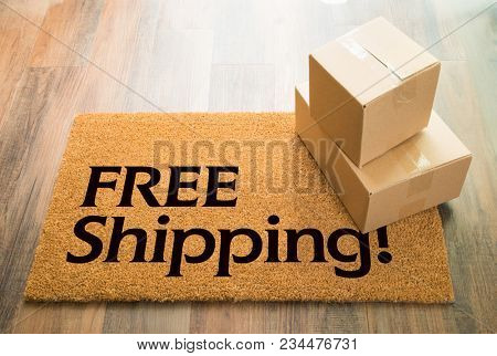 Free Shipping Welcome Mat On Wood Floor With Shipment of Boxes.