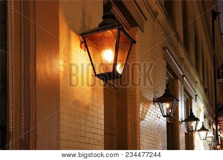 Night Street View With Glowing Real Gas Lanterns On The Outdoor Wall One Of The Building In The Famo
