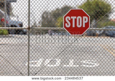 A Stop Sign Attached To Chain Link Fence