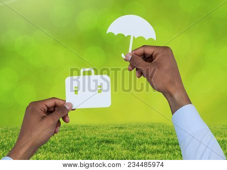 Cut outs of Briefcase and umbrella insurance over grass