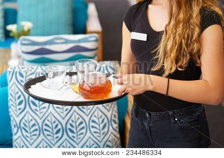 The Waitress Is Carrying Tea. Hospitable Girl Waitress Holding Tray With Cup Of Tea And Tea Glass Te