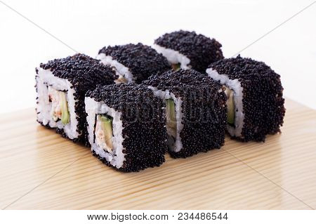 One Set Of California Rolls Covered Black Tobiko Or Masago Caviar On A Wooden Board On A White Backg