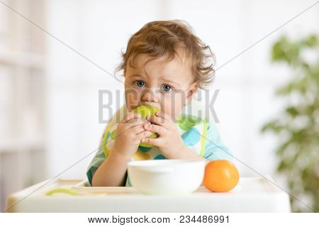Cute Baby Boy One Years Old Sitting On High Children Chair And Eating Fruits Alone In White Kitchen