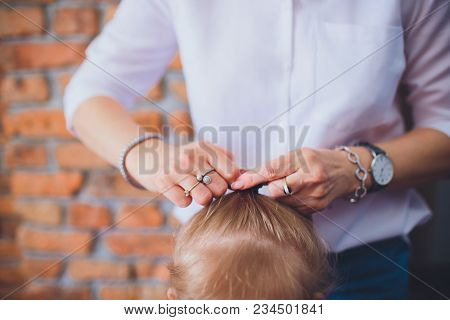 The Hands Mom Braid Pigtails Daughter On A Background Of Red Bricks