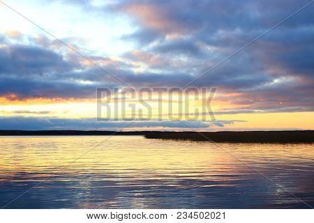 Sunset on the lake. Beautiful sunset nature. Evening landscape. Clouds over the lake. The horizon at sunset. Sea, lake at sunset. The waves on the river. The lake in Russia