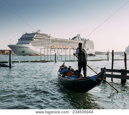 Venice, Italy - March 25, 2018: Juxtaposition Of Gondola And Huge Cruise Ship In Giudecca Canal. Old