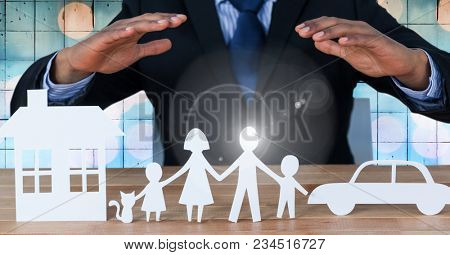 Cut outs of house family and car with mans hands above