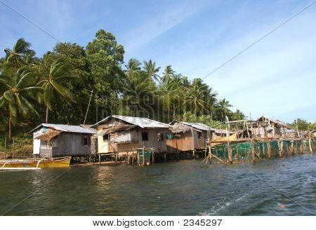 Native Huts Along A River In Philippines