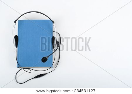Audiobook On White Background. Headphones Put Over Blue Hardback Book, Empty Cover, Copy Space For A