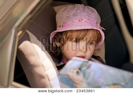 Girl In Safety Seat Looking Over Window Pane