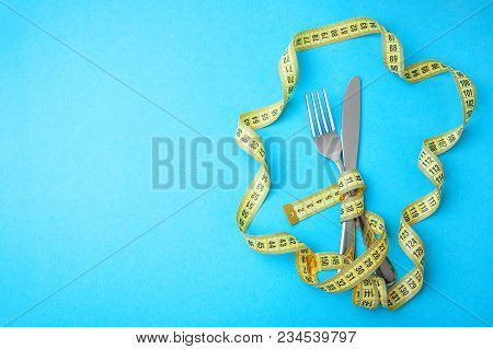Hunger Strike As Way To Lose Weight. The Fork And Knife Are Wrapped In Yellow Measuring Tape On Blue