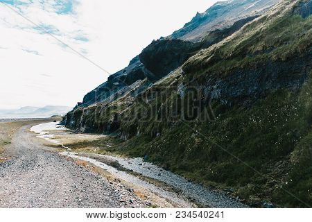 Beautiful Icelandic Landscape With Rocky Hills And Green Vegetation With Flowers