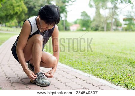 Senior Woman Jogger Tighten Her Running Shoe Laces
