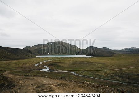 Small River From Melting Water, Rocky Hills With Green Vegetation And Lake In Iceland
